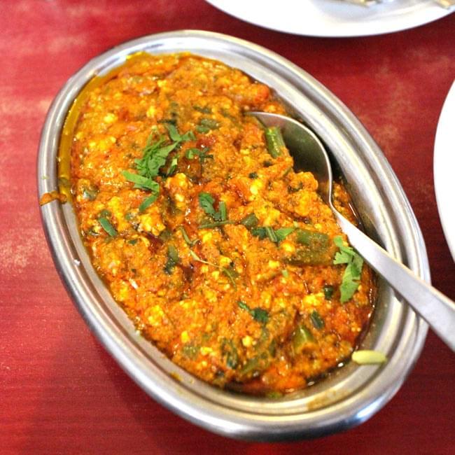 【冷めにくい!二層式】インドのステンレスと銅製 オーバルプレート[約21.8cm×15cm]の写真6 - 同ジャンルのオーバル型プレートの使用例です。インドでは一つのお皿に数人分のカレーを入れ、何人かで取り分ける時にも使います。もちろん、カレーとご飯の一人分用にもちょうどいいですよ!