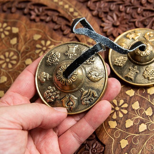 幸運の八吉祥柄ディンシャ【約6.5cm】の写真5 - こちらの革紐を使って振り子のように揺らし鳴らします
