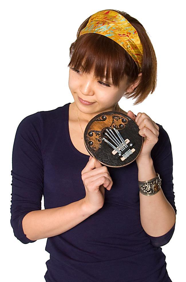 7弦ココナッツカリンバ 【ナチュラル・小】の写真7 - 女性が持ってみるとこれくらいの大きさです(こちらは同じくらいの大きさの、別の商品です)