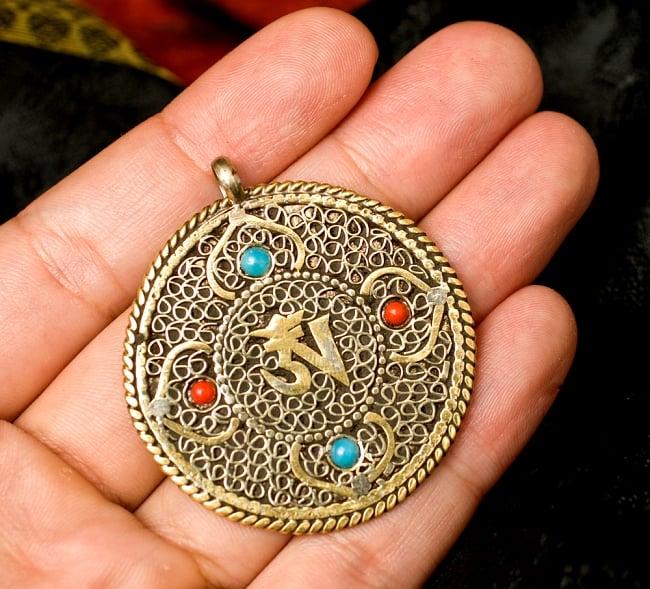 青と赤の石のヴァジュラとオーンのペンダント(革紐付き) 4 - 手に持つとこんな感じです