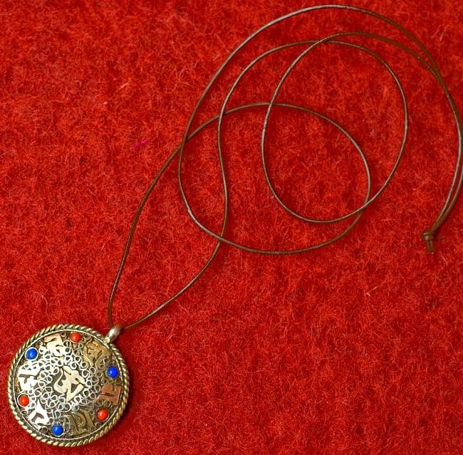 青と赤の石のヴァジュラとオーンのペンダント(革紐付き) 5 - 紐を通してみました(イメージはID-ACS-258のものです)