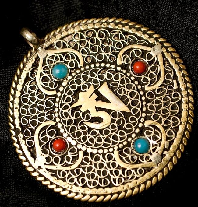 青と赤の石のヴァジュラとオーンのペンダント(革紐付き)の写真