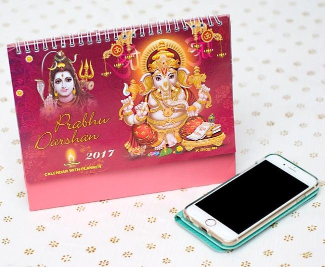 【2017年度版】インドの卓上カレンダー Prabhu Darshanの写真7 - 携帯電話と比べてみるとこれくらいの大きさです。机の上に飾ってあるだけでありがたい、素敵な素敵なカレンダーです!