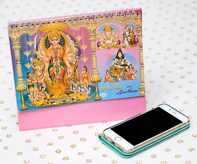 【2017年度版】インドの卓上カレンダー Prabhu Aradhanaの写真7 - 携帯電話と比べてみるとこれくらいの大きさです。机の上に飾ってあるだけでありがたい、素敵な素敵なカレンダーです!