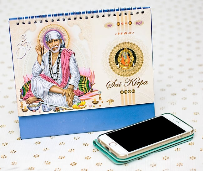 【2017年度版】インドの卓上カレンダー Sai Kirpaの写真7 - 携帯電話と比べてみるとこれくらいの大きさです。机の上に飾ってあるだけでありがたい、素敵な素敵なカレンダーです!