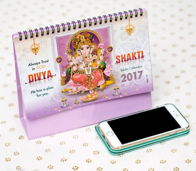 【2017年度版】インドの卓上カレンダー Divya Shaktiの写真7 - 携帯電話と比べてみるとこれくらいの大きさです。机の上に飾ってあるだけでありがたい、素敵な素敵なカレンダーです!
