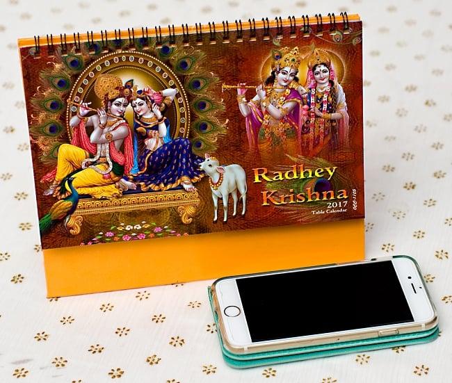 【2017年度版】インドの卓上カレンダー Radhey Krishnaの写真7 - 携帯電話と比べてみるとこれくらいの大きさです。机の上に飾ってあるだけでありがたい、素敵な素敵なカレンダーです!