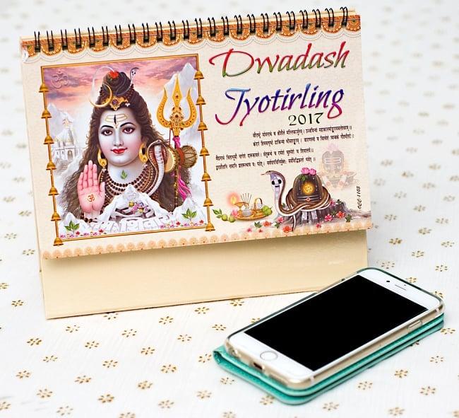 【2017年度版】インドの卓上カレンダー Dwadash Jyotirlingの写真7 - 携帯電話と比べてみるとこれくらいの大きさです。机の上に飾ってあるだけでありがたい、素敵な素敵なカレンダーです!