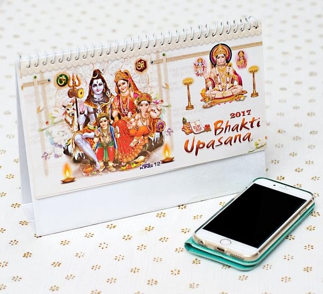 【2017年度版】インドの卓上カレンダーBhakti Upasanaの写真7 - 携帯電話と比べてみるとこれくらいの大きさです。机の上に飾ってあるだけでありがたい、素敵な素敵なカレンダーです!