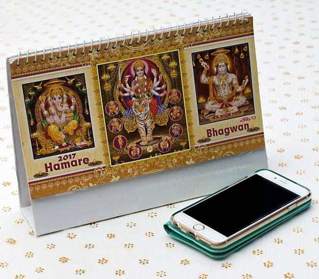 【2017年度版】インドの卓上カレンダー Hamare Bhagwanの写真7 - 携帯電話と比べてみるとこれくらいの大きさです。机の上に飾ってあるだけでありがたい、素敵な素敵なカレンダーです!