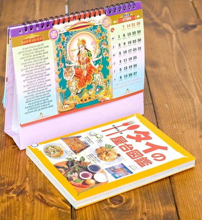 【2018年度版】インドの卓上カレンダー Radha Krishnaの写真7 - 縦20cmx横15cmの本と比べてみるとこれくらいの大きさです。(同時サイズの類似商品となります)