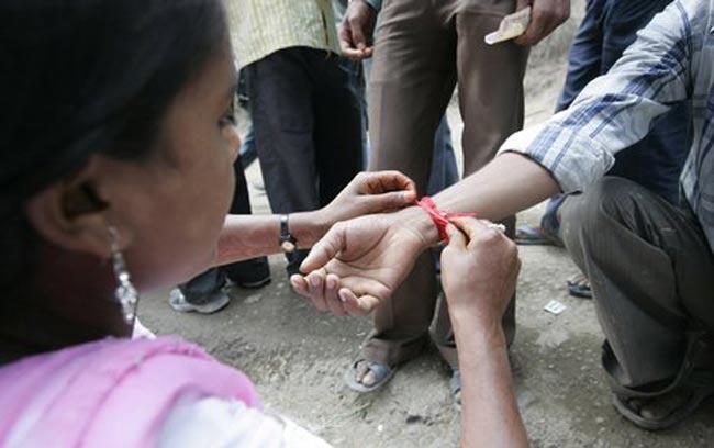 幸運の紐 - ラーキー 2 - インドでラーキーを結んでいるところ