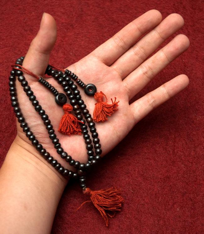 ネパールの数珠 - 飾りつき(黒)の写真4 - サイズを感じていただく為、手に載せてみたところです。