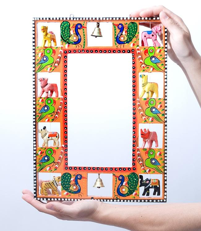 インドの動物 鏡&フォトフレーム【大・水色】の写真8 - 大きさの参考のため、男性スタッフが両手で持ってみました。こちらは同じ大きさのカラー違いの商品(オレンジ)です。