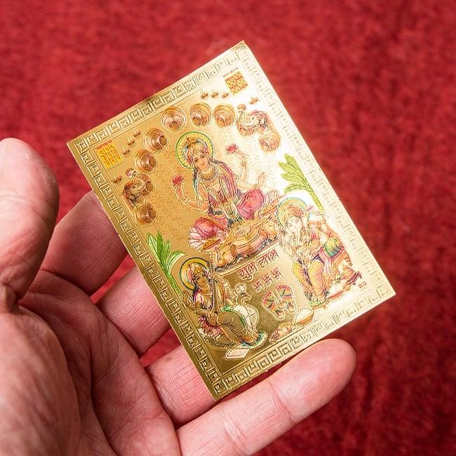 〔約6cm×約8.5cm〕インドのヒンドゥー神様ゴールドお守りカード ステッカー - ラクシュミ・サラスヴァティ・ガネーシャ 4 - 光を受けて明るく輝くカードです