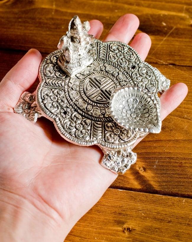 ガネーシャのホワイトメタル丸皿お香立ての写真7 - サイズ比較のために手に持ってみました