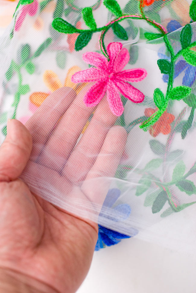 〔50cm切り売り〕花とつる草のレース生地 - 白〔幅約115cm〕の写真5 - 端のほうを手で持ってみました。手芸などに幅広くお使いください。