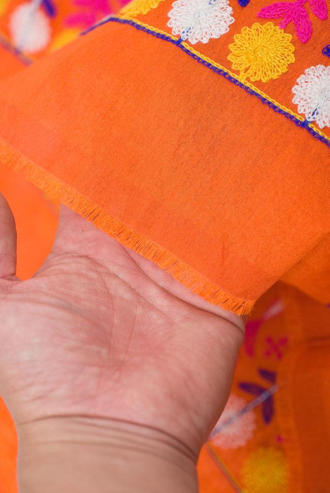〔50cm切り売り〕ラジャスタンの刺繍布 - オレンジ〔幅110cm〕の写真9 - 端の部分を手で持ってみました。適度な薄手の生地に刺繍が施されています。