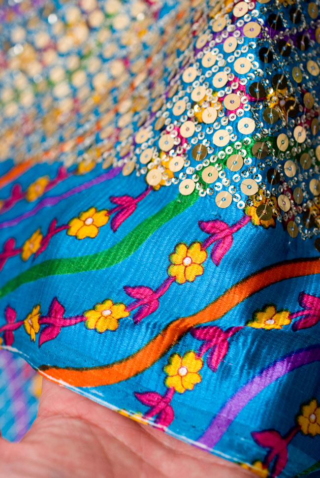 〔1m切り売り〕インドのスパンコールクロス - 水色〔幅約100cm〕 5 - 端のほうを手で持ってみました。つややかな生地の上にスパンコールが施されています。