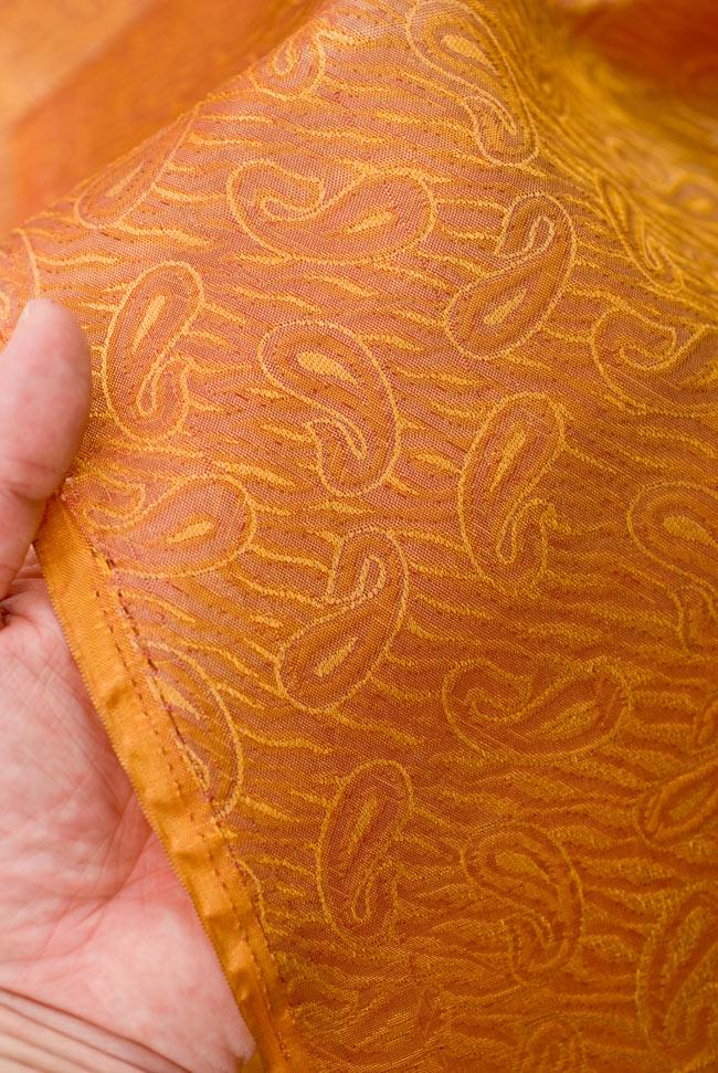 〔1m切り売り〕インドの伝統模様布 - 橙地にペイズリー〔幅112cm〕の写真4 - 端のほうを手で持ってみました。適度な薄手の生地で、使いみちに広がりがあります。