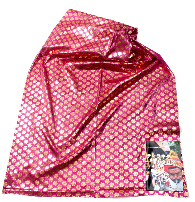 〔1m切り売り〕インドの伝統柄ゴールドプリント光沢布〔幅約110cm〕 - 紫の写真6 - 布を広げてみたところです。横幅もしっかり大きなサイズ。右下にあるのはサイズ比較用の当店A4サイズカタログです。
