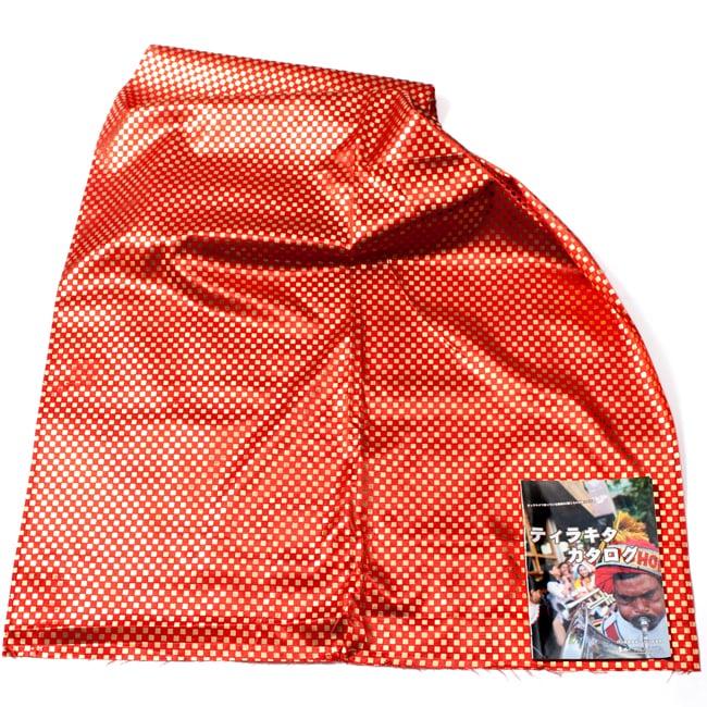 〔1m切り売り〕市松模様ゴールドプリント光沢布〔幅約105cm〕 - オレンジ 6 - 色違いの布を広げてみたところです。横幅もしっかり大きなサイズ。右下にあるのはサイズ比較用の当店A4サイズカタログです。