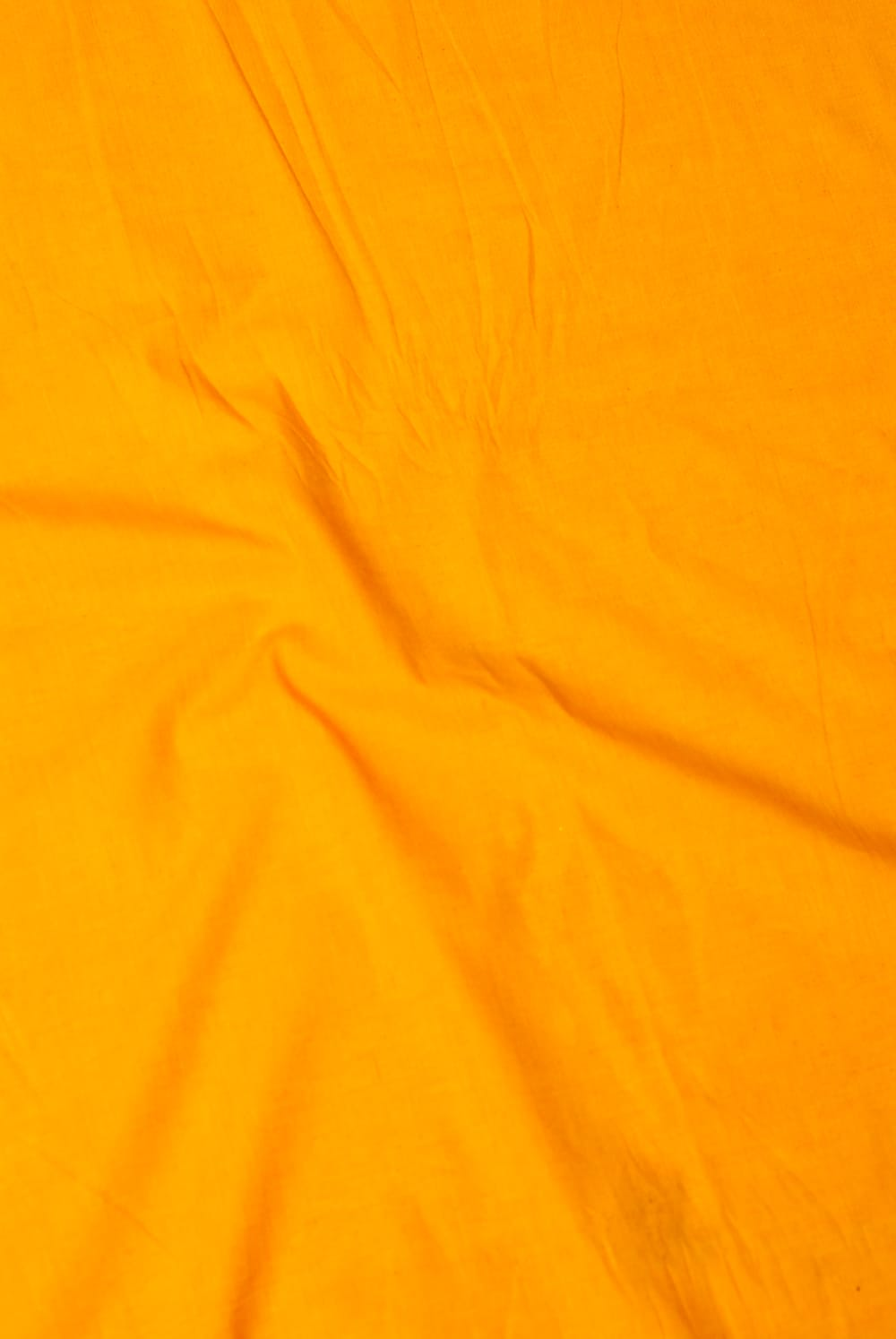 〔1m切り売り〕インドのシンプルコットン布  - オレンジイエロー〔幅約113cm〕 2 - やや離れてみました。無地で使いやすい布地です。