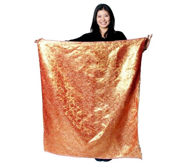 〔1m切り売り〕インドの金糸入り伝統模様布〔114cm〕 - サーモンピンク 7 - 同じインドからやってきた『【MB-RSCLTH-332】〔1m切り売り〕インドの伝統柄ゴールドプリント光沢布〔幅約100cm〕 - ピンク』を、1mカットしてモデルさんに持ってもらった写真です。切り売りの布は基本的に横幅100cm前後と大きいので、ご覧の通り色々な用途に使えそうです。ご注文個数に応じた長さにカットしてお送りいたします。