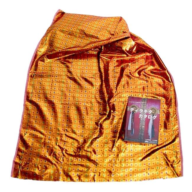 〔1m切り売り〕インドの金糸入り伝統模様布〔102cm〕 - イエロー 6 - 同ジャンル品の布を広げてみたところです。横幅もしっかり大きなサイズ。布の上に置かれているのはサイズ比較用の当店A4サイズカタログです。