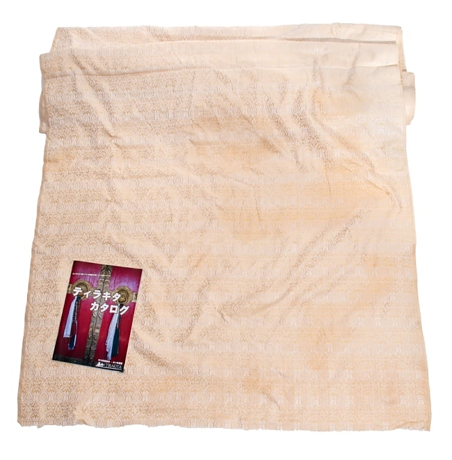 〔1m切り売り〕インドの伝統模様布〔110cm〕 - ゴールドの写真6 - 布を広げてみたところです。横幅もしっかり大きなサイズ。布の上に置かれているのはサイズ比較用の当店A4サイズカタログです。