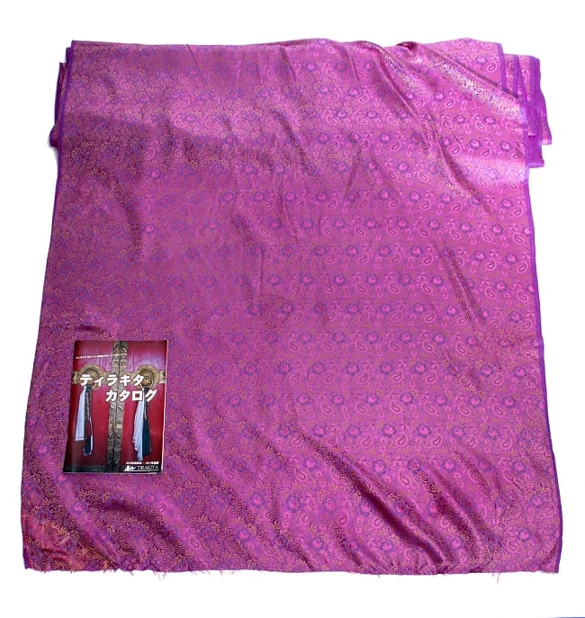 〔1m切り売り〕インドの伝統模様布〔114cm〕 - 赤紫の写真6 - 布を広げてみたところです。横幅もしっかり大きなサイズ。布の上に置かれているのはサイズ比較用の当店A4サイズカタログです。