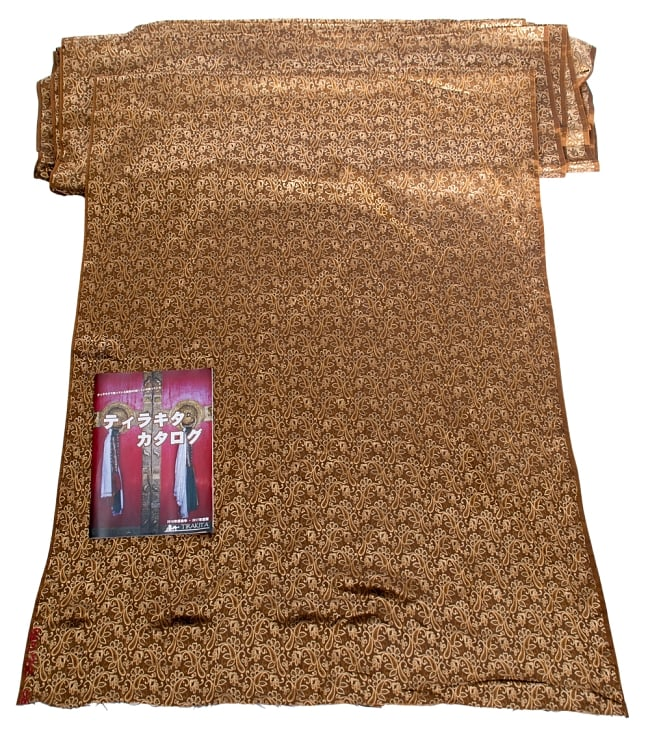 〔1m切り売り〕インドの伝統模様布〔99cm〕 - ブラウンの写真6 - 布を広げてみたところです。横幅もしっかり大きなサイズ。布の上に置かれているのはサイズ比較用の当店A4サイズカタログです。