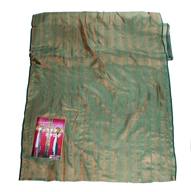 〔1m切り売り〕インドの伝統模様布〔112cm〕 - 緑×ゴールド系の写真6 - 布を広げてみたところです。横幅もしっかり大きなサイズ。布の上に置かれているのはサイズ比較用の当店A4サイズカタログです。