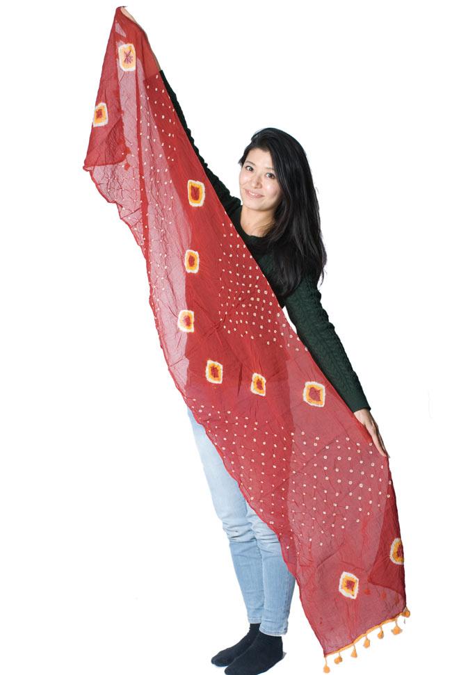 大きな模様の絞り染めドゥパッタ - 黒(赤フリンジ) 7 - 同じ大きさの商品を女性スタッフが広げて持ってみました。大きさのご参考にどうぞ。